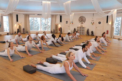 Tantra Student's perform bhujangasana in guided tantra yoga class